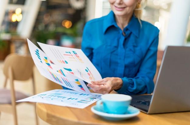 Vista frontale della donna più anziana di affari che si occupa di documenti pur avendo caffè