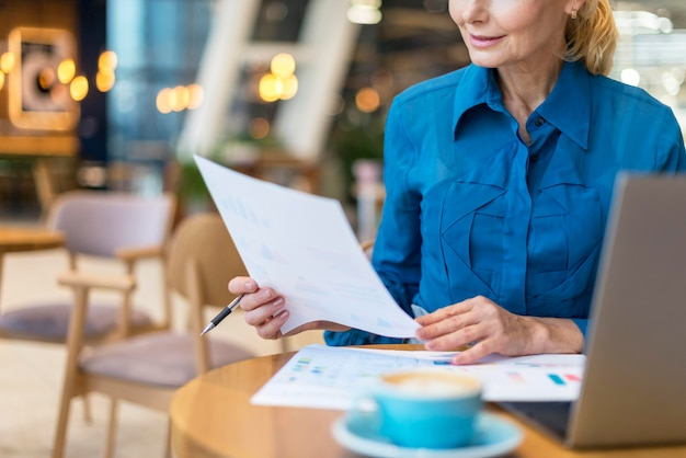 Front view of older business woman dealing with papers