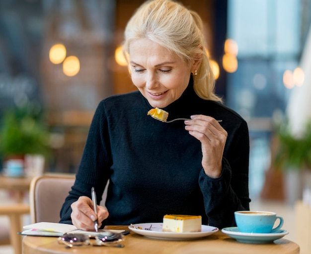 Vista frontale della donna più anziana di affari che mangia dessert mentre si lavora