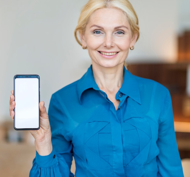 Front view of older business woman holding smartphone