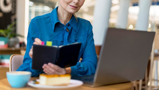 Front view of older business woman with glasses writing in agenda and looking at laptop
