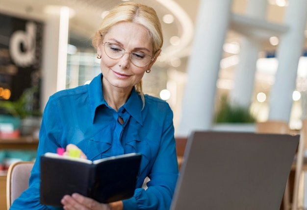 Front view of older business woman with glasses writing in agenda