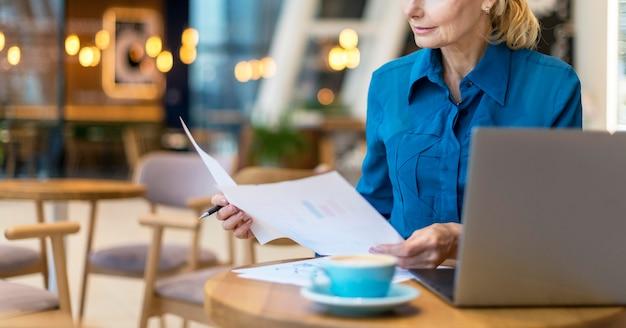 Vista frontale della donna più anziana di affari che lavora con documenti e laptop