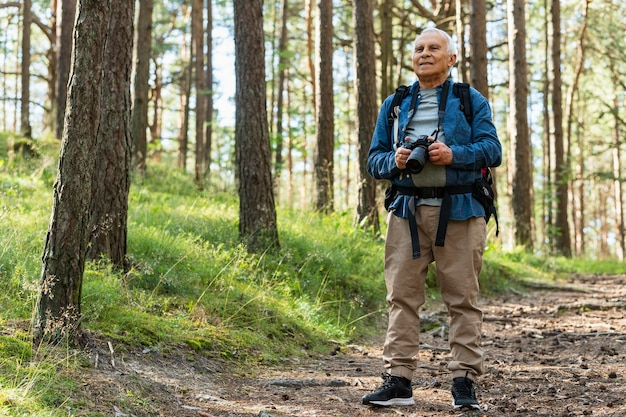 Front view of older man exploring nature with camera