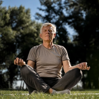 Front view of older man in lotus position outdoors during yoga