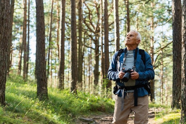 Front view of older man with backpack exploring nature