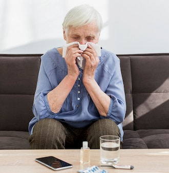Front view of older woman blowing her nose