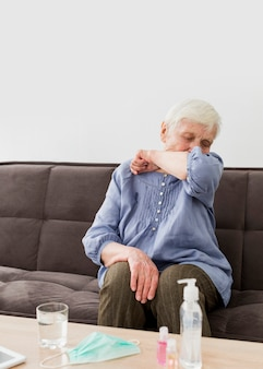 Front view of older woman coughing while at home
