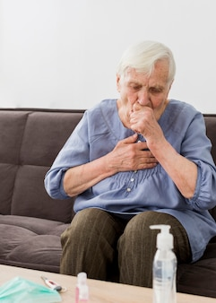 Front view of older woman coughing