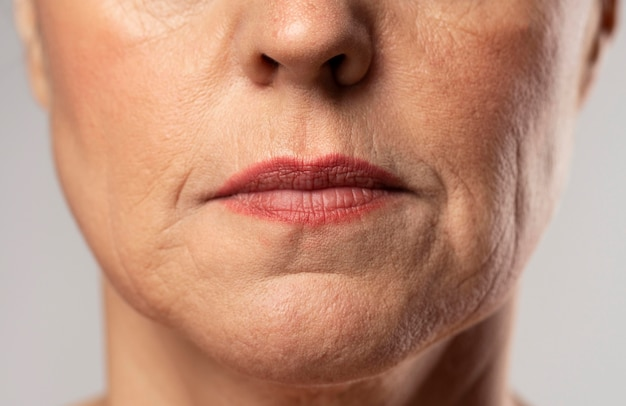 Front view of older woman posing stoic with make-up on
