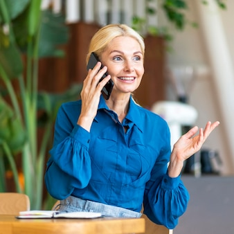 Vista frontale della donna anziana che parla al telefono mentre si lavora