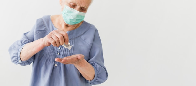 Front view of older woman using hand sanitizer with copy space