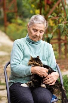 Vista frontale della donna anziana con il gatto presso la casa di cura
