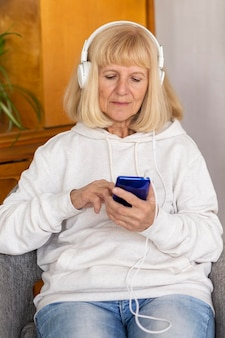 Front view of older woman with headphones and smartphone