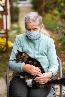 Vista frontale della donna anziana con maschera medica e gatto in casa di cura
