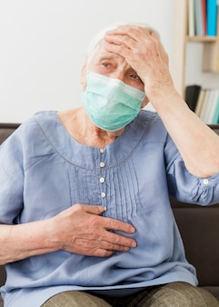 Front view of older woman with medical mask feeling ill