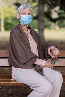 Vista frontale della donna anziana con maschera medica e disinfettante per le mani