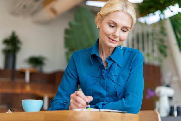 Vista frontale della donna anziana al lavoro con penna e taccuino