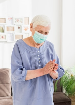 Front view of older women with medical mask praying