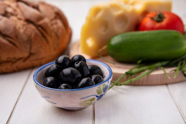 Front view olives with cheese  tomato  cucumber on a stand  with a loaf of black bread on a white background
