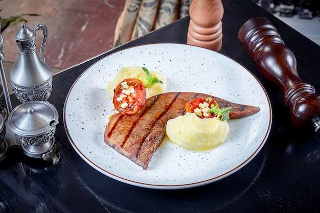 Вид спереди на стейк из говяжьего языка с картофельным пюре и помидорами на гриле, подается на белой тарелке. премиум японский говяжий язык. японский стейк вагью. русская кухня. барбекю еды. пищевой фон