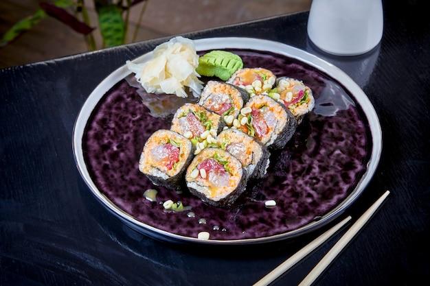 참치 orsalmon와 매운 롤에 전면 모습. suchi. 일본 음식 스타일. 해물. 건강하고 균형 잡힌 다이어트 식사. 스시 롤 어두운 접시에 설정합니다. 공간, 음식 배경 복사