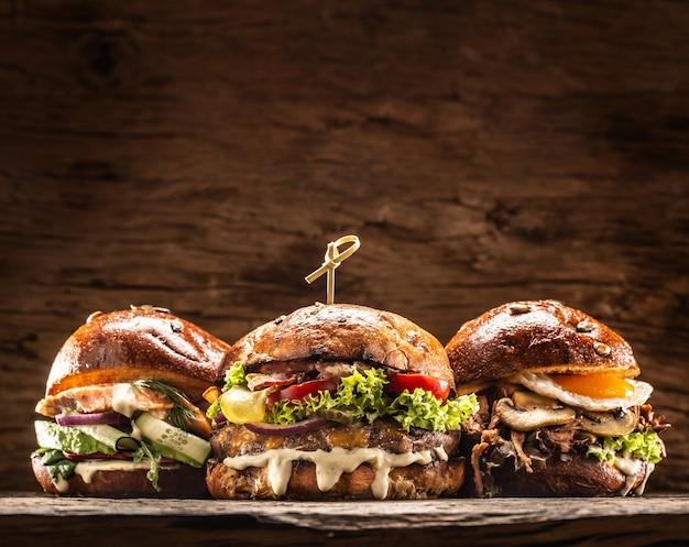 新鮮な野菜のサラダとドレッシングを詰めた3つの大きなビーフサーモンとケバブのハンバーガーの正面図。