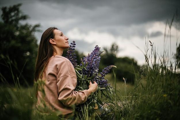 Vista frontale di una bella ragazza con un enorme mazzo di lupini viola selvatici, vestita con abiti casual in una giornata nuvolosa