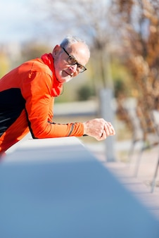 Front view of one senior runner man with sportswear sitting on a wooden fence while looking camera