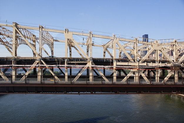 Front view of one side of the queensboro bridge at noon with transit of vehicles leaving