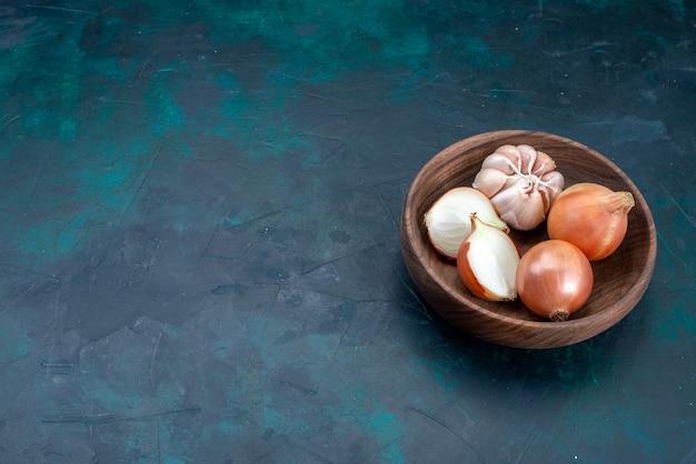 紺色の机の上のタマネギとニンニクの正面図野菜の食事食品の健康