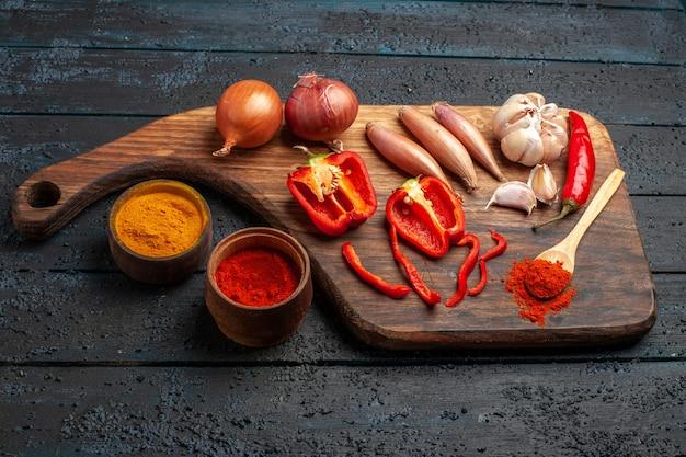 Cipolle di vista frontale e aglio con condimenti sulla scrivania scura