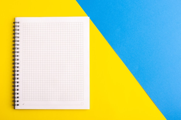 Front view open blue copybook blank paper on yellow-blue surface