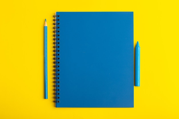 Front view open blue copybook with pencil on the yellow desk