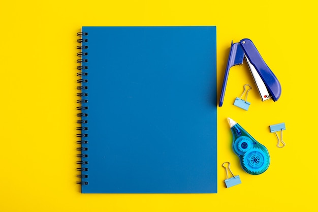 Front view open blue copybook with stickers on yellow surface