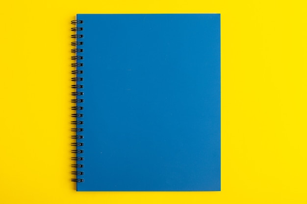 Front view open blue copybook on yellow desk