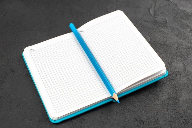 Vista frontale del taccuino blu aperto e della penna su nero