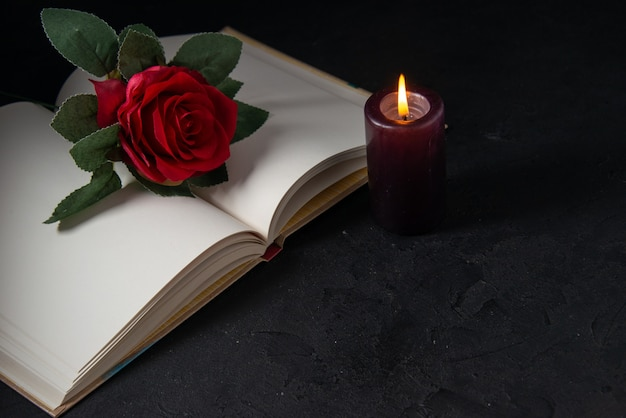 Front view of open book with candle and red flower on black