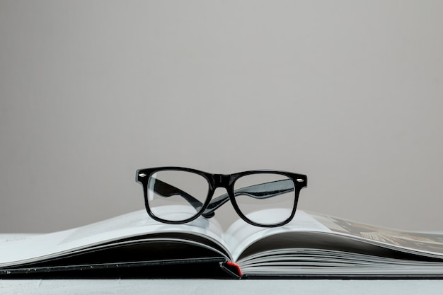 Front view open book with glasses