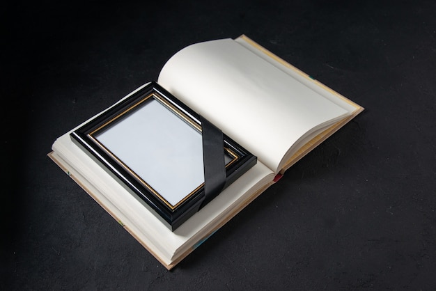 Front view of open book with picture frame on black