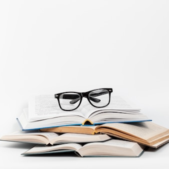 Front view open books with glasses