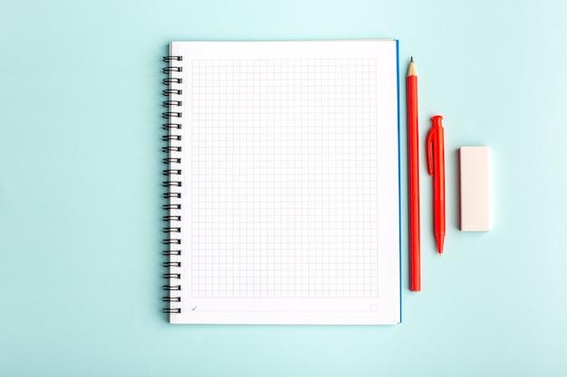 Вид спереди открытая тетрадь с ручкой и карандашами на синей поверхности