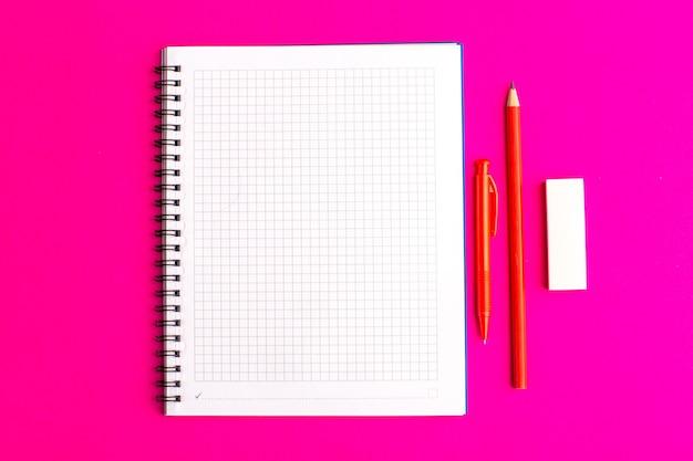 Quaderno aperto vista frontale con penna e matite sulla superficie viola