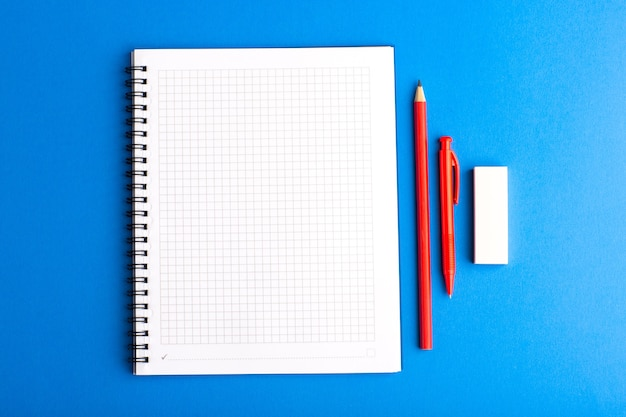 Front view open copybook with pencil on blue surface