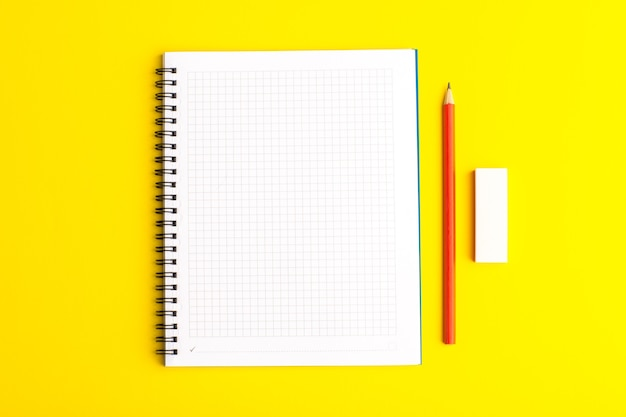 Front view open copybook with pencil on yellow surface