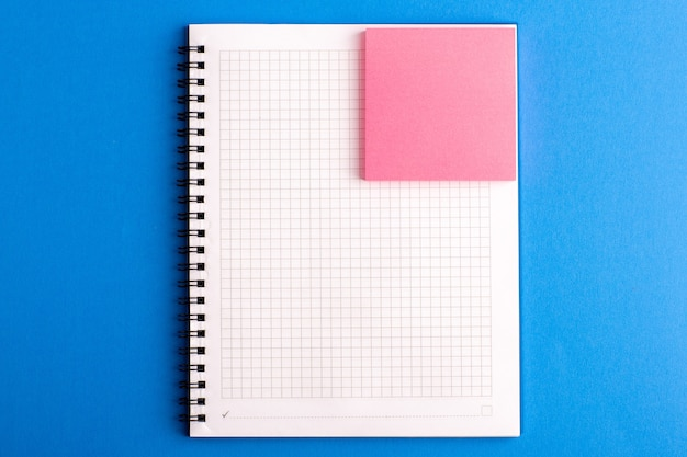 Front view open copybook with pink sticker on the blue desk