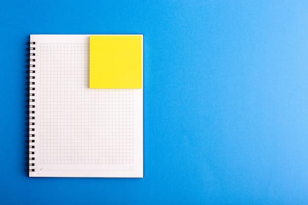 Quaderno aperto vista frontale con adesivo sulla superficie blu