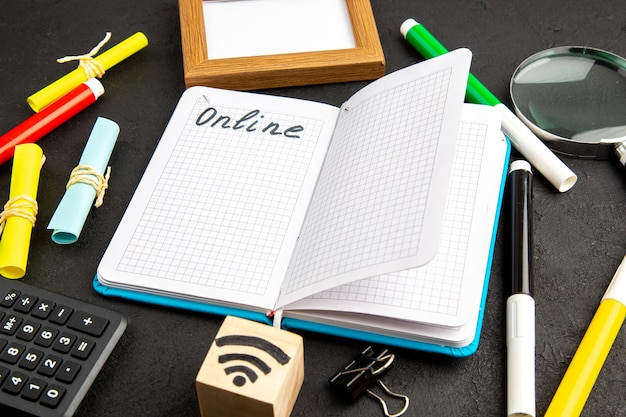Front view open copybook with writing and pencils