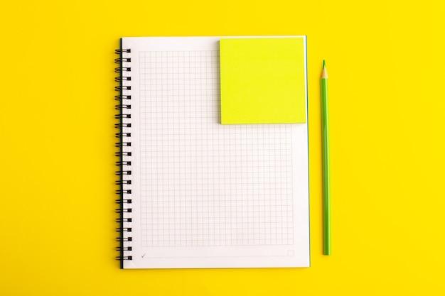 Вид спереди открытая тетрадь с желтой наклейкой на желтом столе