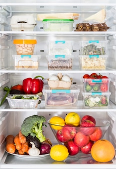 Front view of open fridge with casseroles and vegetables